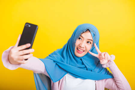 Asian Muslim Arab, Portrait of happy beautiful young woman Islam religious wear veil hijab funny smile she taking making selfie with smart mobile phone, studio shot isolated on yellow background