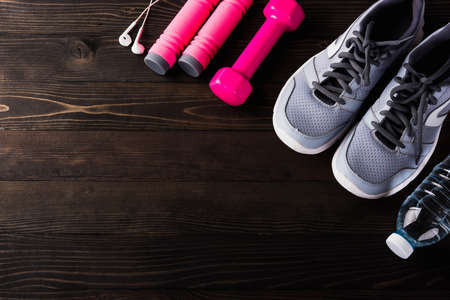 Pair sports shoes, headphones, dumbbell and water bottle on black wood table background, Gray sneakers and accessories equipment in fitness GYM, Healthy workout active lifestyle diet concept