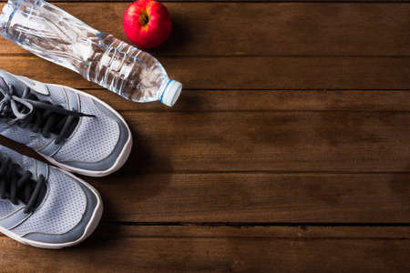 Top view of pair sports shoes, bottle water and red apple on wood table, Gray sneakers and accessories equipment in fitness GYM, Healthy workout concept Stockfoto