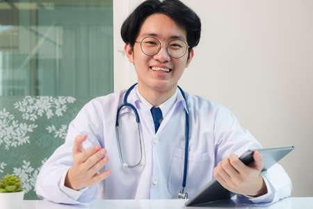 Happy Asian young doctor handsome man smile wear glasses use modern smart digital tablet computer explain patients symptoms of illness on desk at hospital office, Technology Healthcare And Medicine