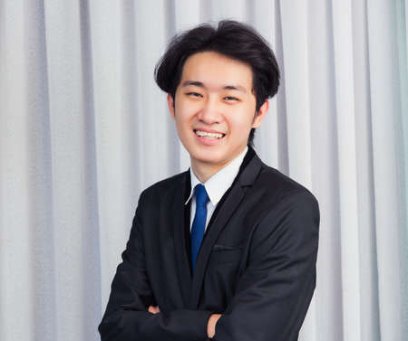 Portrait closeup of happy Asian young handsome manager professional business man laughing confident mature standing in suit smiling looking to camera with copy space