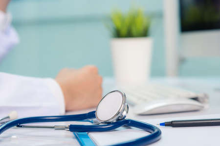 Medicine doctor's working on desk. Closeup of Stethoscope. Hand of man physician video call raise hands to greet patients on table front computer monitor at hospital office, Healthcare medic concept Stockfoto