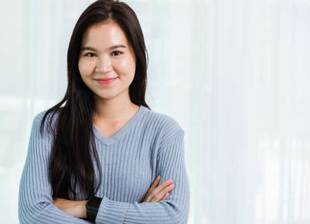 Close up headshot portrait young Asian happy beautiful woman healthy smiling face long hair stand crossed arm, studio shot looking to camera at home and have a copy space
