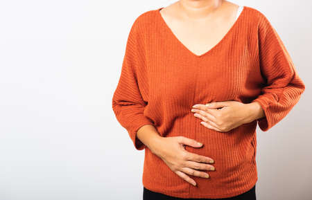 Asian woman she sick have stomach ache holds hands on abdomen, part of body, female having painful stomachache she abdomen bloating or chronic gastritis, studio shot isolated on white background