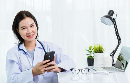 Asian doctor young beautiful woman smiling using working or holding with smart mobile phone and laptop computer at hospital desk office, technology healthcare medical concept