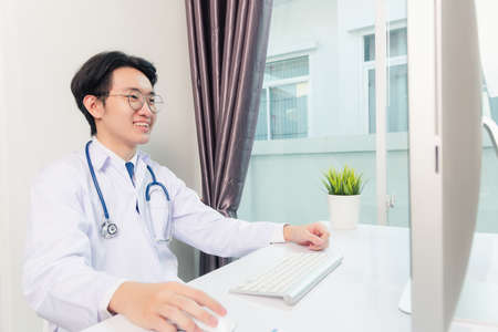 Asian young handsome doctor man wearing a doctor's dress and stethoscope video conference call or facetime with computer to patient he smiling sitting on desk at hospital office, Health medical care