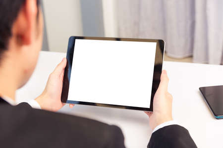 Work from home, Back view of Asian young businessman smile wearing suit video conference call or facetime by smart digital tablet computer blank screen on desk