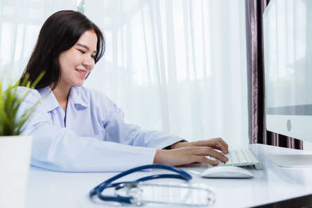 Asian beautiful female doctor smiling wearing doctor's uniform with stethoscope typing on keyboard desktop computer looking to monitor on the desk at hospital office, Medical healthcare concept Stockfoto
