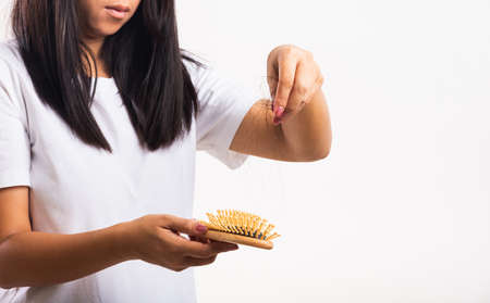 Asian woman unhappy weak hair problem her hold hairbrush with damaged long loss hair in the comb brush she pulls loss hair from the brush, isolated on white background, Medicine health care concept Stockfoto