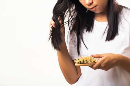 Asian woman unhappy weak hair her hold hairbrush with damaged long loss hair in the comb brush on hand and she looking to hair, studio shot isolated on white background, medicine health care concept