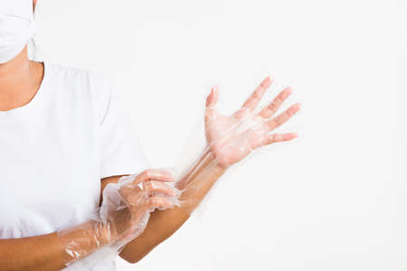 Woman hand wearing single use protect disposable transparent plastic glove, studio shot isolated on white background