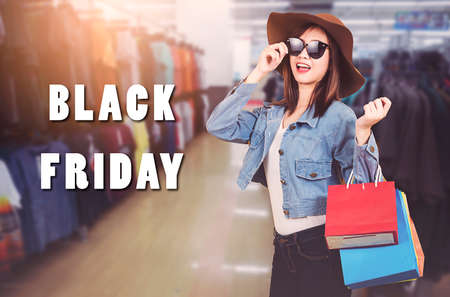 Happy portrait beautiful young woman teen smiling standing with sunglasses and hat she excited holding shopping bags multi color on the mall with copy space, Black Friday sale concept Stockfoto