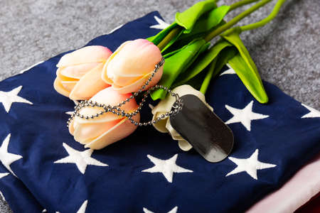 Traditional folded of America United States flag, tag and tulip flower, memorial remembrance and thank you of hero, studio shot with copy space concrete board background, USA Veterans day concept 版權商用圖片