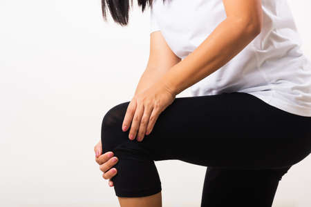 Closeup young woman aches to suffer from pain knee and she uses hand joint hold knee agony, studio shot isolated on white background Rheumatism healthcare and medical physiotherapy therapy concept