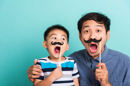 Family funny happy hipster father and his son kid holding black mustache props for the photo booth close face, studio shot isolated on a blue background, November men health awareness