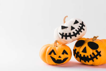 Funny Halloween day party concept ghost pumpkin head jack lantern scary smile and stack together, studio shot isolated on white background, Holiday decoration Stock Photo