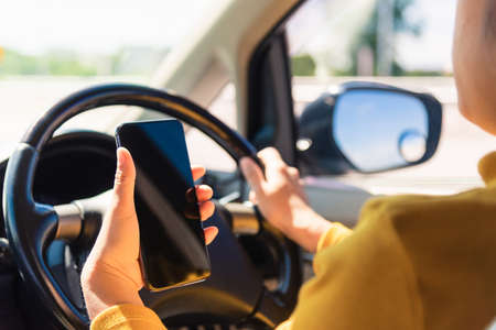 Asian woman inside a car and using a hand holding mobile smartphone blank screen while driving the car in the morning during going to work on highway, Transportation and vehicle concept