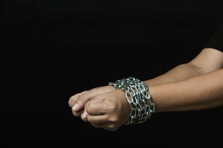 Slave woman she was hand tethered interpreter tied up with steel chain black background. Freedom speech censorship and stop talk, International Human Right day Foto de archivo