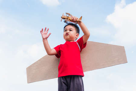 Happy Asian funny child or kid little boy smile wear pilot hat play and goggles with toy cardboard airplane wing flying hold plane toy outdoor against summer blue sky cloud background, Startup freedom