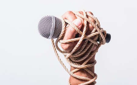 Hand holding microphone and have roped on fist hand on white background, Human rights day concept