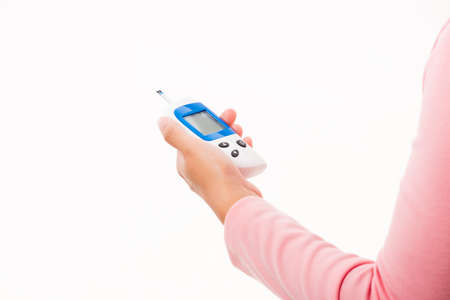 Closeup hand woman measuring glucose test level checking on finger by glucometer she monitor and control high blood sugar diabetes and glycemic health care medical concept isolated on white background