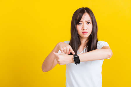 You are late not on time, Portrait Asian of a happy beautiful young woman scared casual girl showing and pointing finger her wristwatch studio shot isolated on yellow background Фото со стока