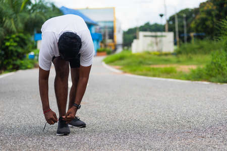Close up Asian sport runner black man standing he trying shoelace running shoes getting ready for jogging and run at the outdoor street health park, healthy exercise workout concept Standard-Bild