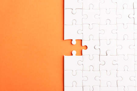 Top view flat lay of paper plain white jigsaw puzzle game texture last pieces for solve and place, studio shot on an orange background, quiz calculation concept