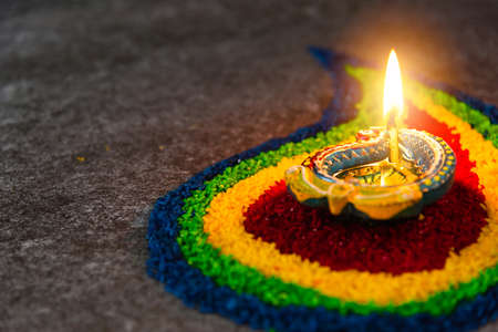 Close up clay lit light a fire already on Diya or oil lamp on concrete background, Decoration of Hinduism rangoli, Happy celebration Deepavali, or Diwali Indian festival concept