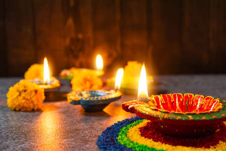 Close up clay lit light a fire already on Diya or oil lamp with flowers on concrete background, Decoration of Hinduism rangoli, Happy celebration Deepavali, or Diwali Indian festival concept