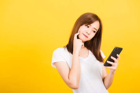 Asian happy portrait beautiful cute young woman teen standing wear t-shirt her using holding smart mobile phone and thinking looking to the phone isolated, studio shot yellow background with copy space
