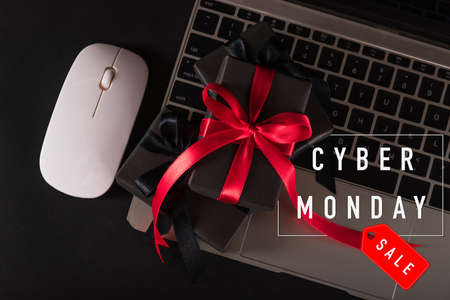CYBER MONDAY sale online shopping concept, Top view of gift box wrapped black paper and red bow ribbon present on a laptop computer keyboard, studio shot on black background 免版税图像