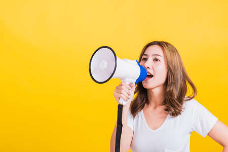 Asian Thai happy portrait beautiful cute young woman stand to make announcement message shouting screaming in megaphone looking to side away, studio shot isolated on yellow background with copy space