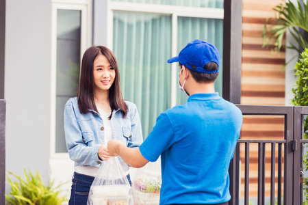 Asian young delivery man wear face mask he making grocery service giving rice food boxes plastic bags to woman customer receiving door at house after pandemic coronavirus, Back to new normal concept