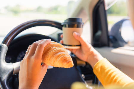 Asian woman eating food fastfood and drink coffee while driving the car in the morning during going to work on highway road, Transportation and vehicle concept 免版税图像