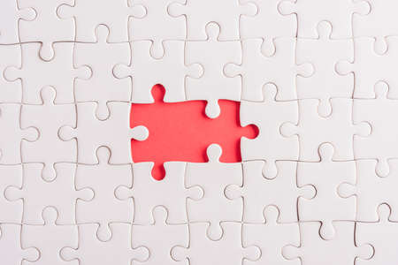 Top view flat lay of paper plain white jigsaw puzzle game texture incomplete or missing piece, studio shot on a red background, quiz calculation concept