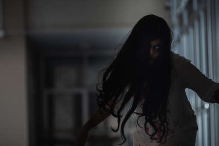 Horror evil woman ghost creepy in a dark room at house. The female devil is scary she haunted at the abandoned building, Happy Halloween day concept