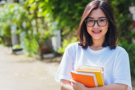 Portrait of Asian teen beautiful young woman wear eyeglasses smile have dental braces on teeth laughing at outdoor she hold education books on hand, Medicine and dentistry concept