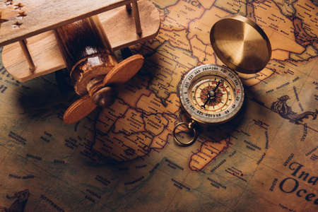 Old compass discovery and wooden plane on vintage paper antique world map background, Retro style cartography travel geography navigation, Columbus Day concept