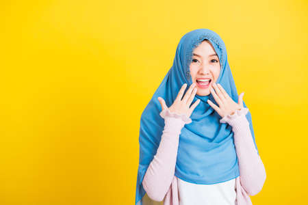Asian Muslim Arab, Portrait of happy beautiful young woman Islam religious wear veil hijab funny smile she shocking open mouth touching her cheeks with hands isolated yellow background