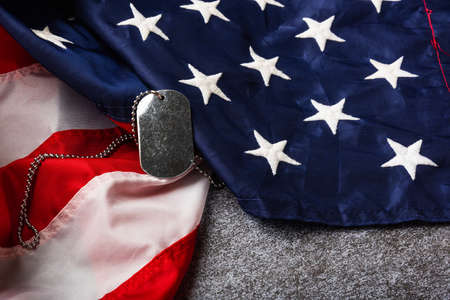 America United States flag and chain dog tags, military symbolizing, studio shot on concrete board background, US Veterans or Independence day concept