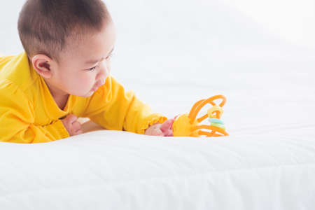 Portrait of beautiful young Asian newborn little baby prone on the bed at home, Happy baby smile wears a yellow shirt relaxing in the room, Family morning at home