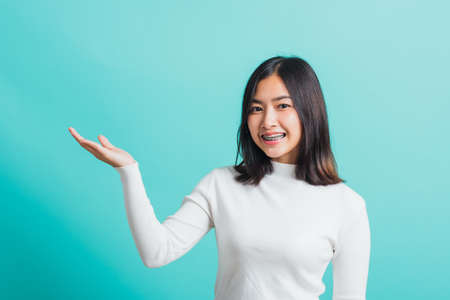 Young beautiful Asian woman smiling makeup showing product on blank hand, Portrait female demonstrate presenting something on hand, studio shot isolated on a blue background Standard-Bild