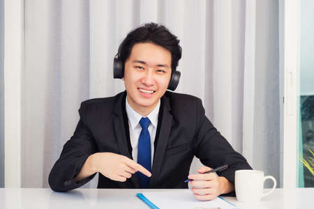 Work from home, Asian young businessman wear suit video conference call or facetime he smiling sitting on desk wearing headphones and raise his hand point finger to a paper job he looking to camera