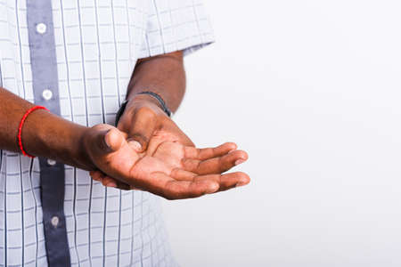 Closeup hand Asian black man holds his palm hand injury, feeling pain, studio shot isolated on white background. Health care and medical office syndrome concept Stockfoto