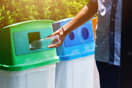 Selective focus close up the man black hand throwing an empty plastic water bottle in the recycling garbage trash or bin, environmental recycling concept