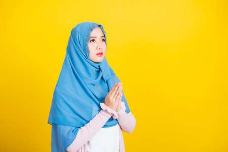 亚洲人穆斯林阿拉伯,愉快的美丽的少妇宗教佩带的面纱hijab她指甲花装饰的手祈祷对安拉上帝,隔绝在黄色背景,Eid穆巴拉克和灵魂禁食