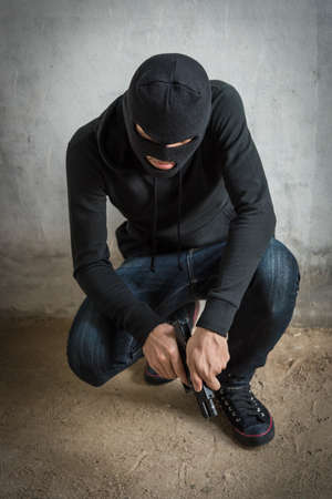Portrait robbery man is holding gun on hand, kidnapping Thief robber