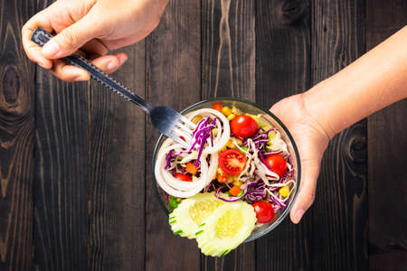 Top view of woman hands holding the healthy colorful salad bowl with fresh mixed greens vegetable in a dish on black wooden background, Health snack food