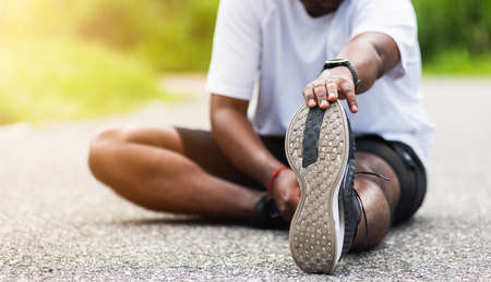 Close up Asian young athlete sport runner black man wear watch he sitting pull toe feet stretching legs and knee before running at outdoor street health park, healthy exercise before workout concept